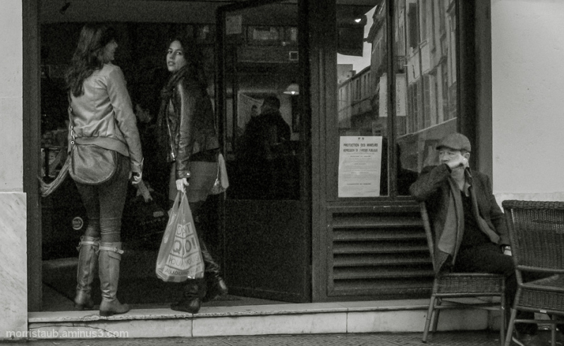 Two young women walking into a restaurant.