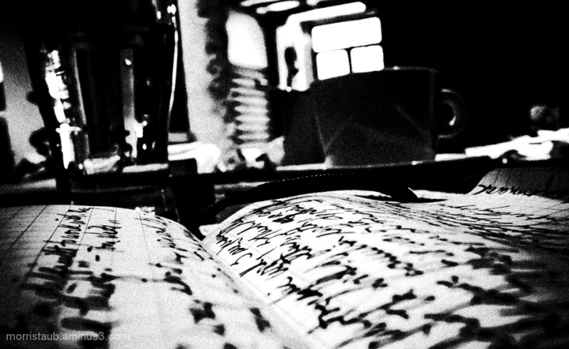 Cafe table with mug milk water and notebook.