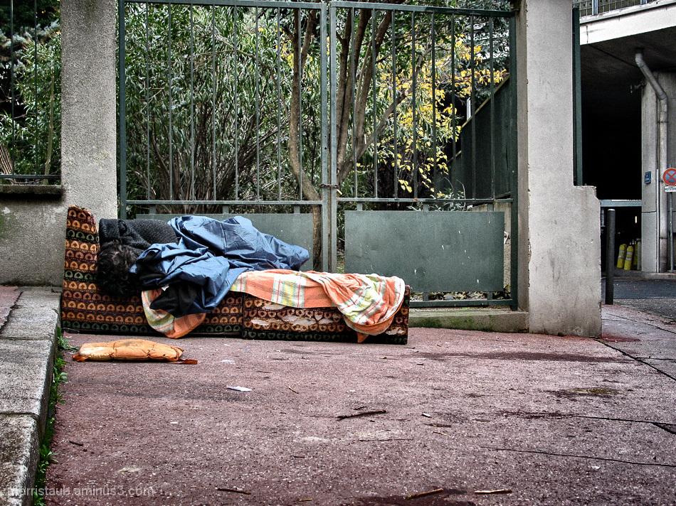 Woman sleeping on a sofa outdoors.