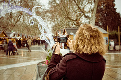Woman taking photo of holiday scene.