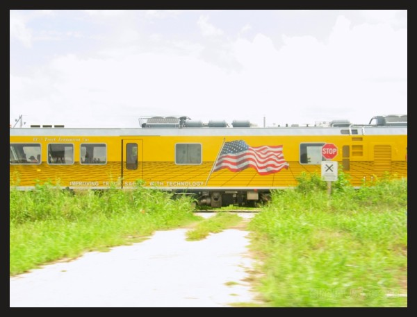 yellow train with flag in front of the road