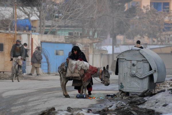 woman picking food scraps, Kabul