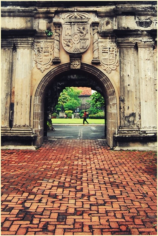 A Walking Man Framed by an Arc at Fort Santiago