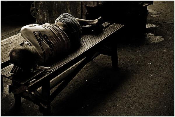 Old Man Sleeping on a Bench at a Manila Sidewalk