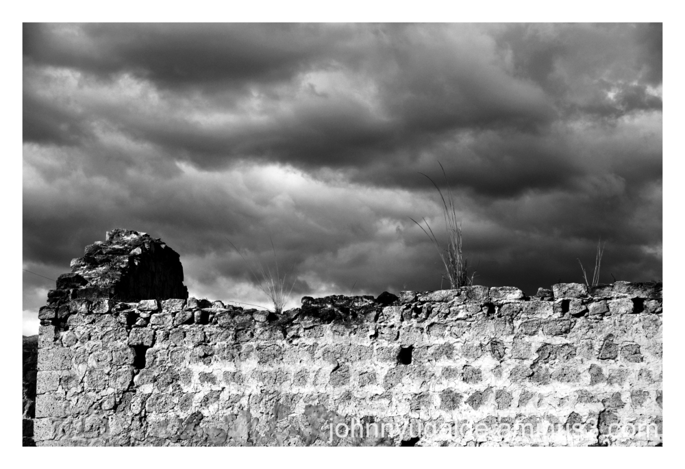 Stormy sky over the old stone wall
