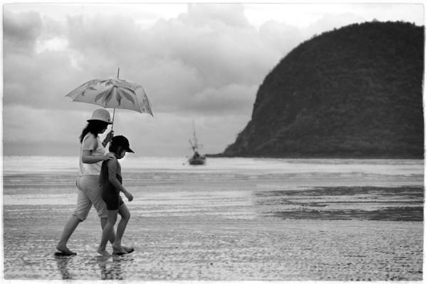 under rain, Mother & daughter walk on the beach