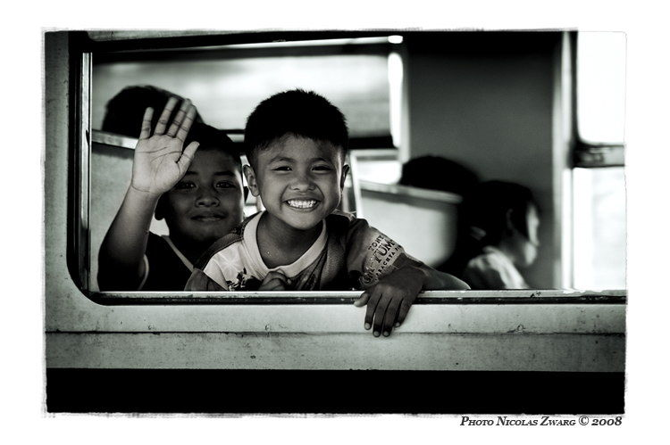 "two thai children waving ""bye bye"" at train window"