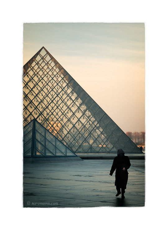 People walking in front of Louvre Pyramid
