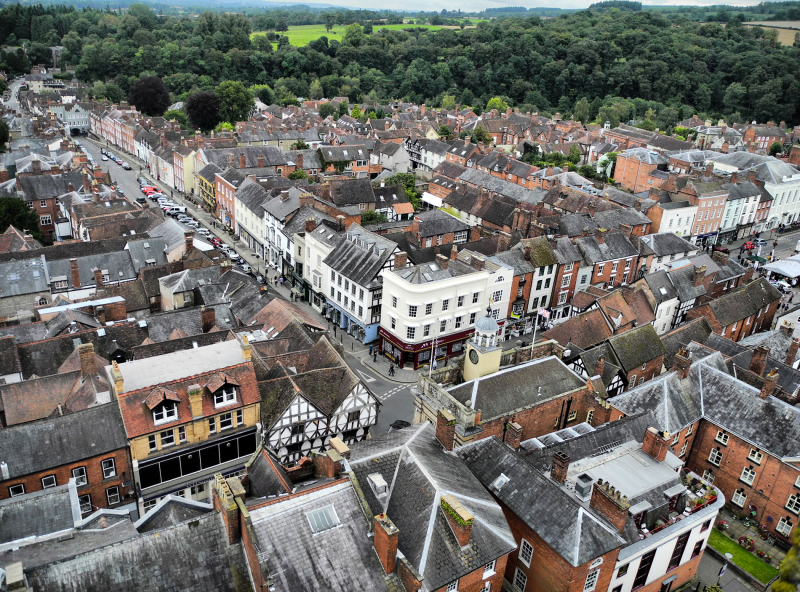 Greetings from Ludlow, England  From the roof of St Laurences Church in Ludlow ( a Market town on the English side of the Welsh borders)  looking almost towards the south with Broad Street running from the centre to the left of the frame.   Most of these rather grand houses started life as hovels and as the town became more affluent got large new façades built on them. The clock tower in the centre is on the Old Butter Cross market building. At the bottom of Broad Street on the left you can just discern the Broad Gate, the only surviving fortified entrance to the town.   I have put this in the Aminus3 Urban photo category, though as a small border town it scarcely makes the grade really :)