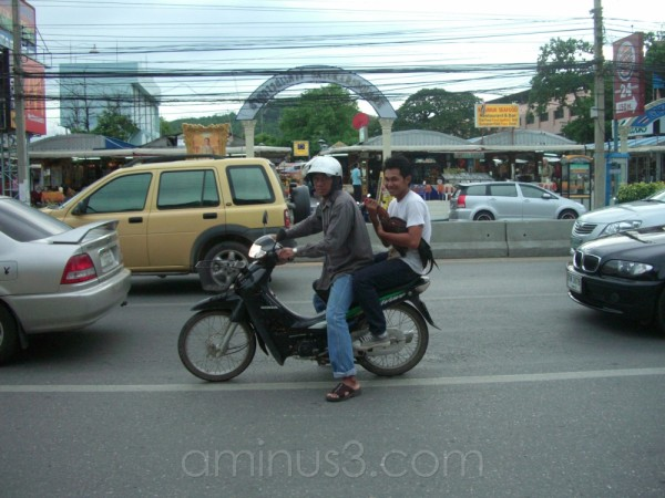 One moped, two men, and a chicken