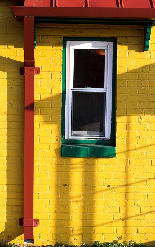 yellow brick building with downspout