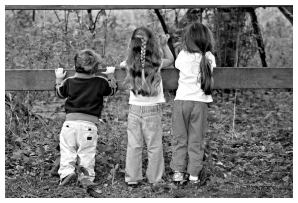 Kids hanging over a fence