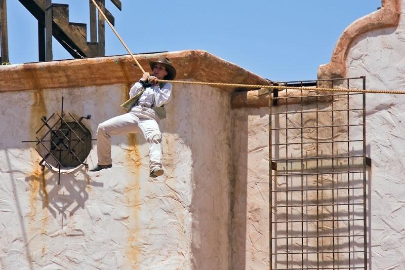 Stunt woman at Old Tucson Studios sliding on rope