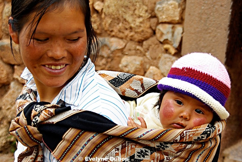 Tender and amused look of a mother. (Bolivia)