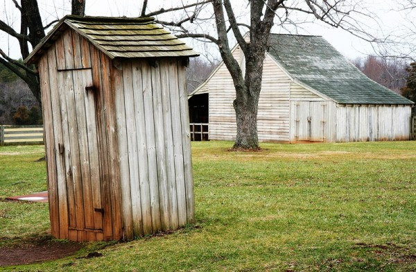 a crooked outhouse in front of a barn