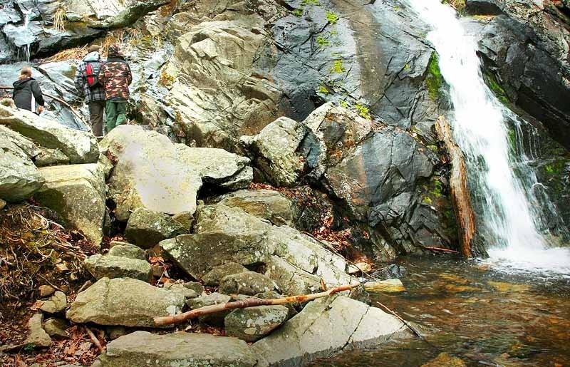man and 2 kids hiking a waterfall