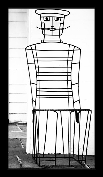 black and white photo of a wire chair