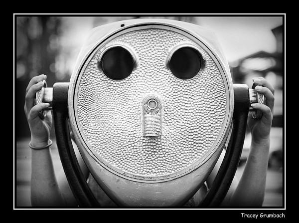 girl looking through large binoculars