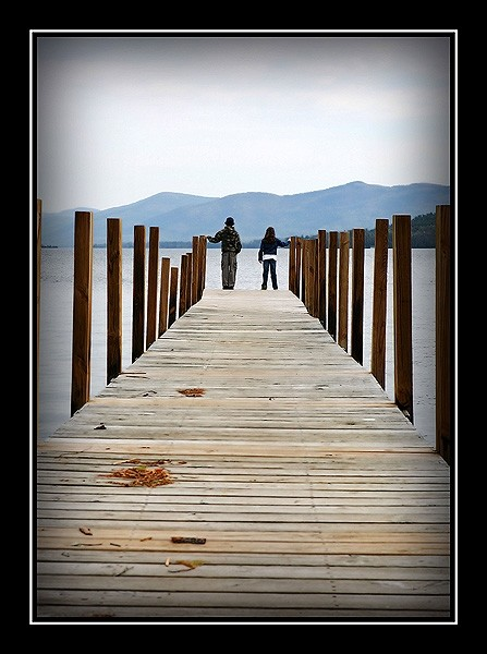 two kids at the end of a long pier
