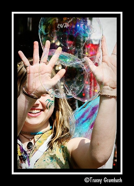 girl reaching to touch bubbles