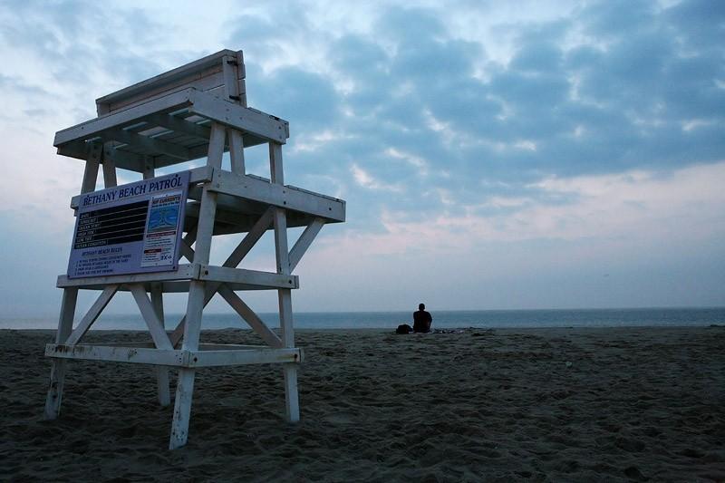 man sitting on beach watching the sky