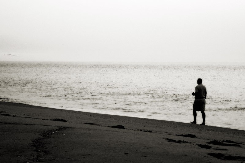 black and white photo man walking on beach at dawn