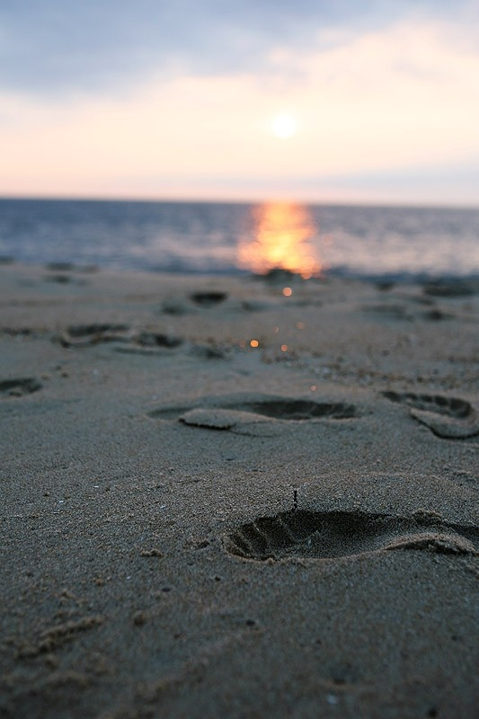 footprints in the sand at sunrise