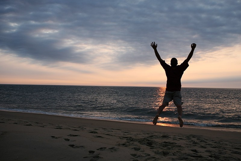 man jumping on the beach at sunrise