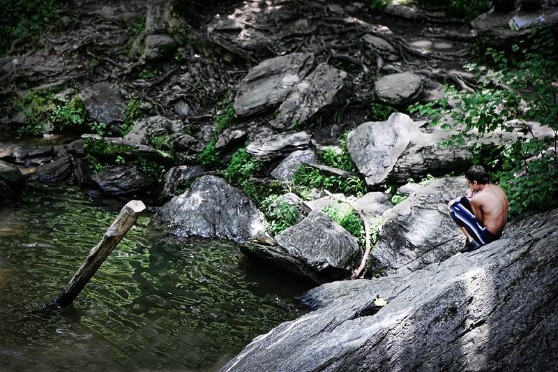 boy sitting on rock near water