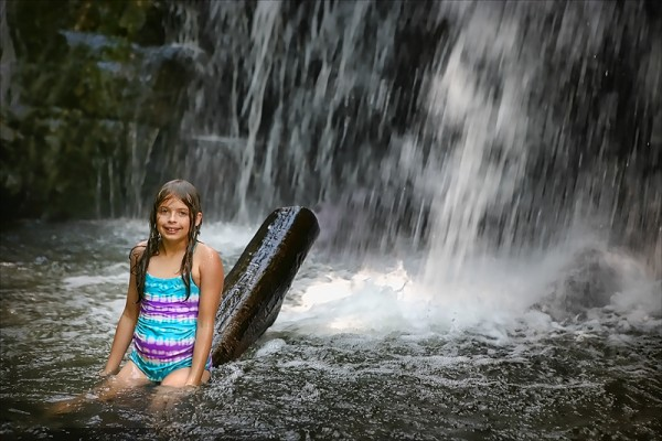 girl in a pool of water in front of waterfall