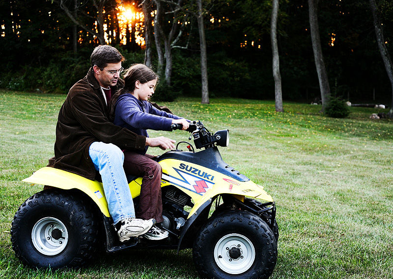 father teaching daughter about 4 wheeler