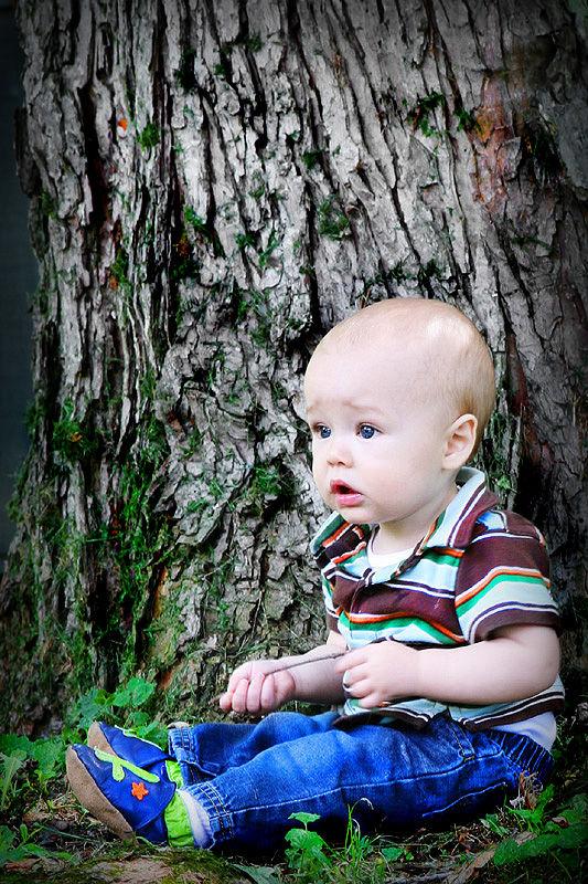 baby boy sitting under tree