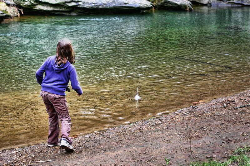 girl skipping rocks
