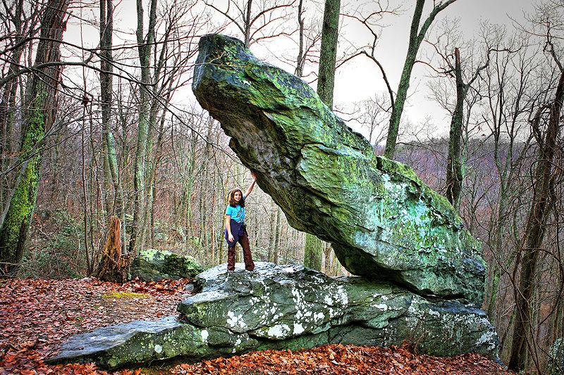 girl holding up large rock