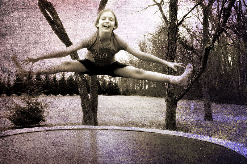 girl doing a split in air on trampoline