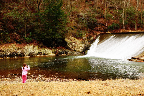 girl photographing a waterfall