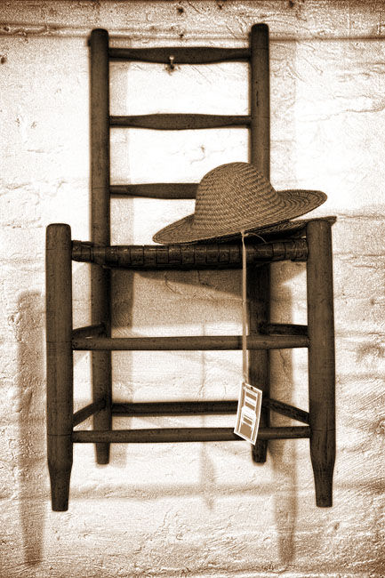 antique chair and hat on wall