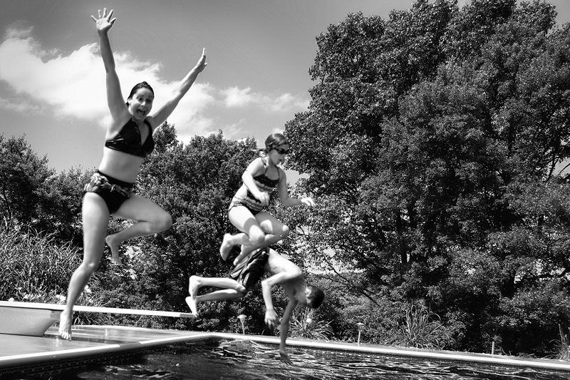 three people jumping into a pool