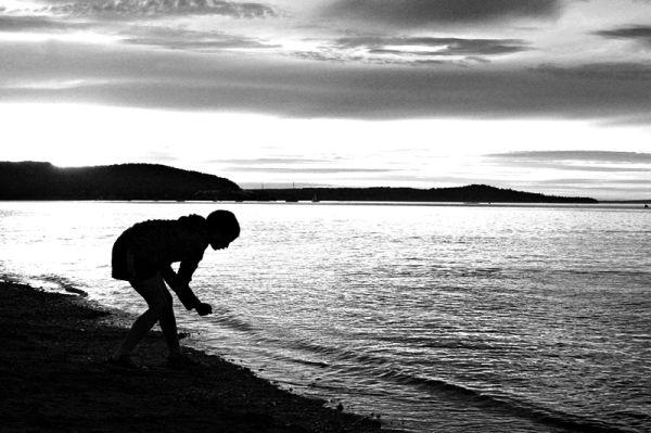 girl searching for a rock at sundown at Bar Harbor