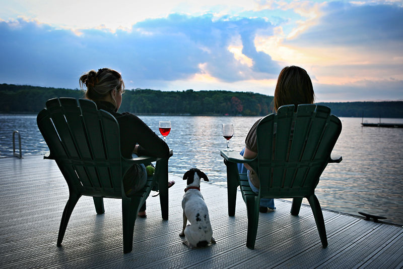 two women and a dog watching the sunset