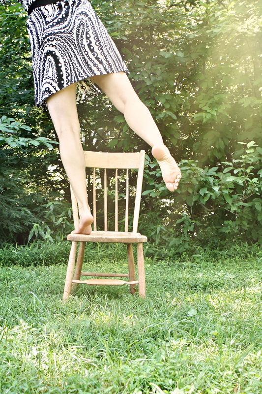 girl balancing on a chair