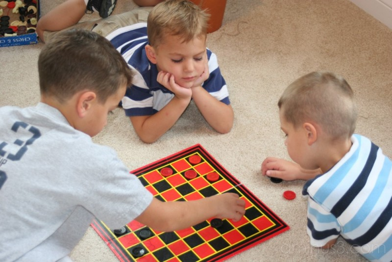 3 young cousins playing checkers together