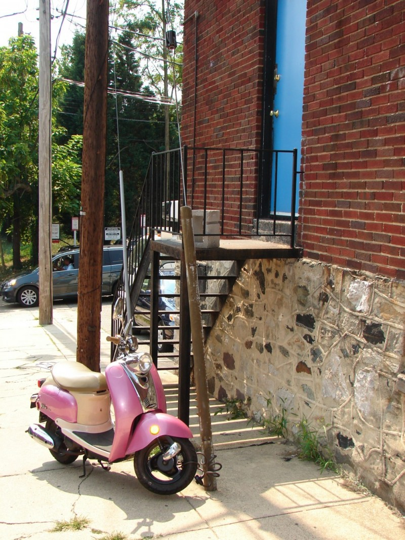 Pink Scooter next to stairs up to a blue door