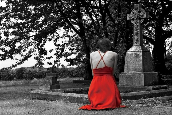 girl in a red dress by a gravestone in b&w