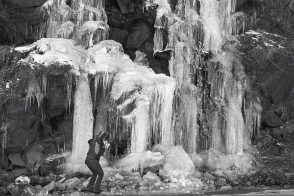 Photographer shooting a frozen waterfall
