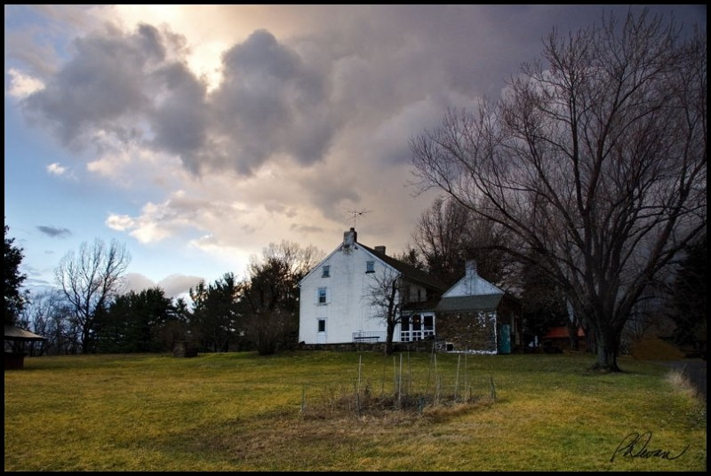 thunderstorm passing over old farmhouse