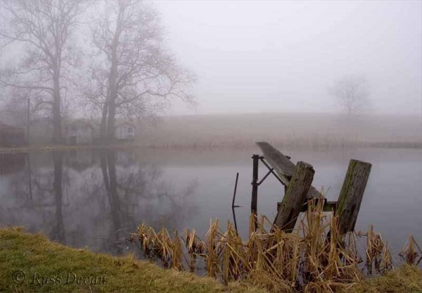 Old diving board on fog-covered farm pond