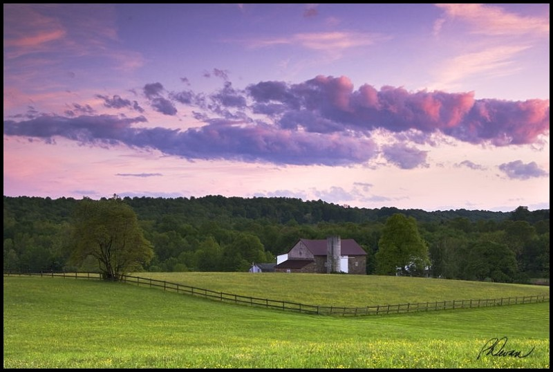 Sunset reflecting off clouds over a farm