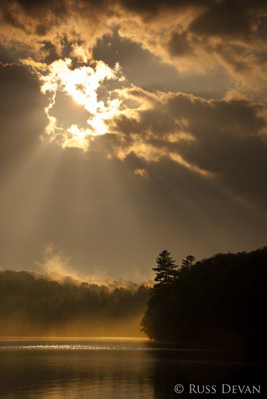 Sunbeams shining through storm cloud of lake