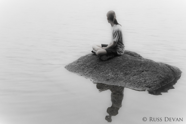 Girl sitting on rock in a foggy lake